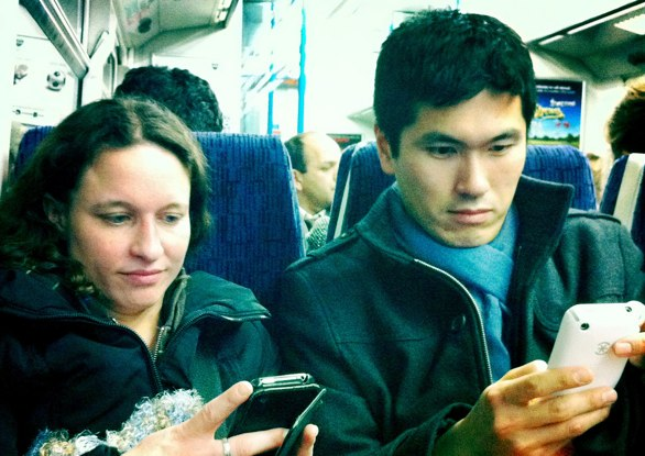 Person accessing the web on a train using an iphone