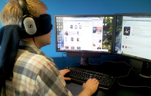 David Ball wearing a blindfold while using his computer.