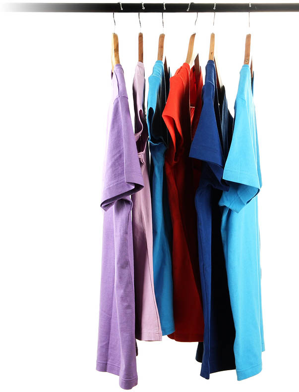 Choice of clothes of different colors on wooden hangers, isolated on white