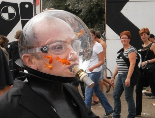 Man wearing a divers helmet containing goldfish