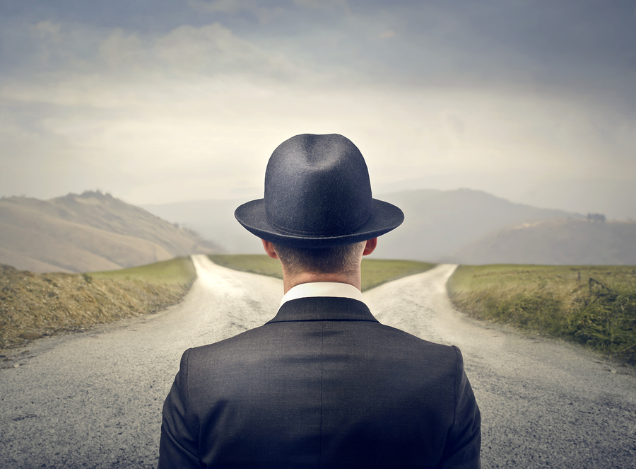 businessman with hat in front of two roads